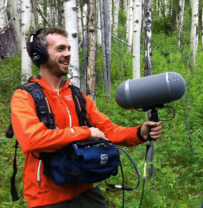 Engineer Rob Byers gathers sound in the woods with an enormous microphone.