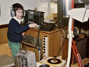 A very young Ryan Noyes in headphones with a stereo.