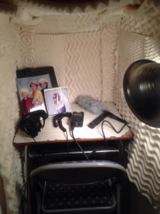 An egg crate-lined closet with audio gear, a small desk, and photos of the Golden Girls and Joan Didion.