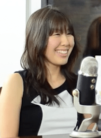 Producer Elizabeth Nakano sits, smiling, in front of a microphone.