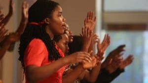 A young, black woman with long hair sings with a choir at a church in in Kansas City, in front of a background of raised hands.