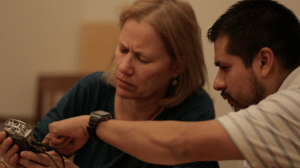 Debby Bussel, a blonde, white woman, examines a recorder as Roberto Nava points to various features at Storymakers training, March 2016. Video still by Ian McClerin.